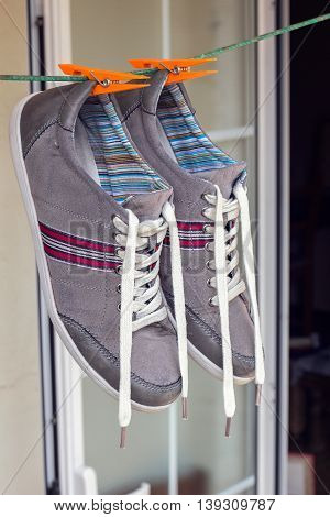 pair of grey sneakers hanging on a clothespin