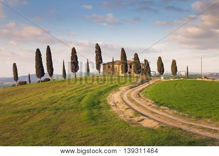 Pienza, Italy - March 17, 2016: House in Tuscany on a hill with cypress trees and a green field in Pienza, Valdorcia (Orcia Valley), Italy.