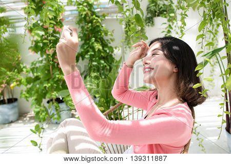 Beautiful asian young woman relaxing on a balcony's garden.