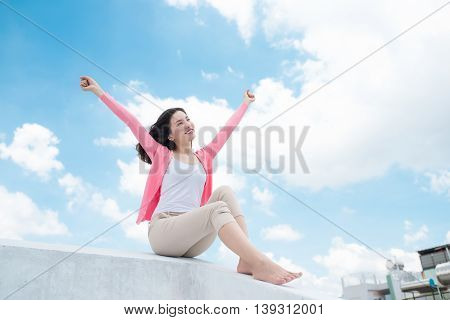 Freedom concept. Enjoyment. Asian young woman relaxing under blue sky on rooftop with her hands raised towards sky