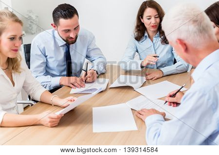 Lawyers having team meeting in law firm reading documents and negotiating agreements