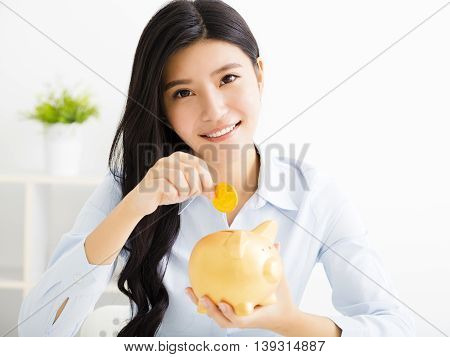 young smiling asian business woman with piggybank