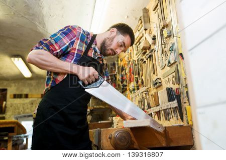 profession, carpentry, woodwork and people concept - carpenter working with saw and wood plank at workshop
