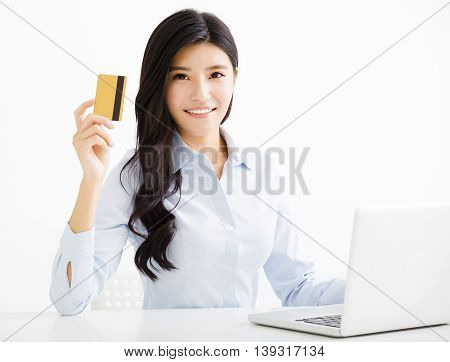 Smiling business woman showing credit card in office