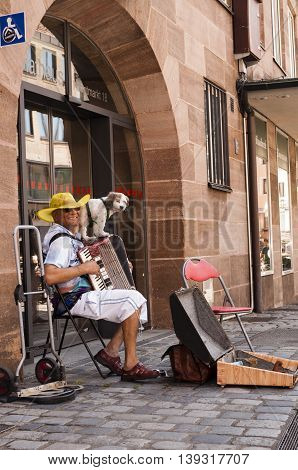Nurnberg Bavaria / Germany - July 19th 2014: photo of a street musician playing his piano accordion on the streets of Nurnberg