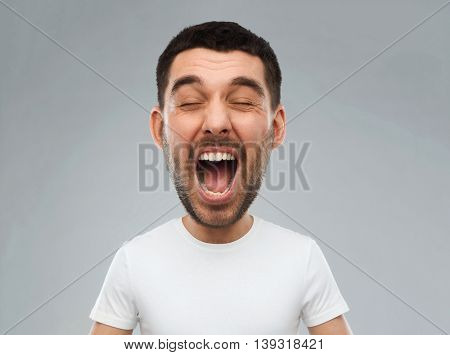 emotions, stress, madness and people concept - crazy shouting man in white t-shirt over gray background (funny cartoon style character with big head)