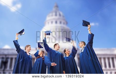 education, graduation and people concept - group of happy smiling students in gowns waving mortarboards over washington white house background