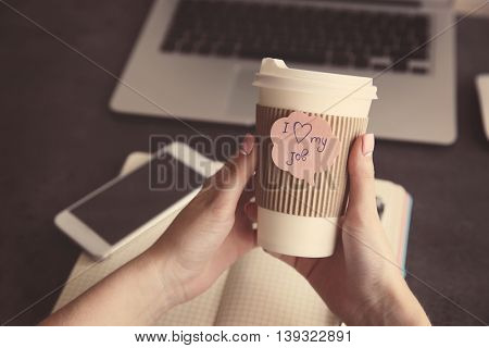 I love my job concept. Female hands holding hot cup of coffee