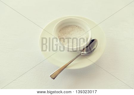 sweetener, carbohydrates, diet and unhealthy eating - sugar bowl and saucer with spoon on table