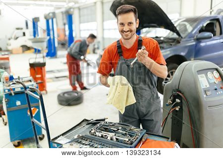 Car mechanic fixing a car in garage at dealership