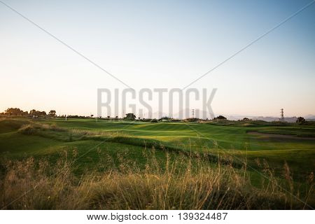Beautiful golf course with sand trap and striped grass at sunset