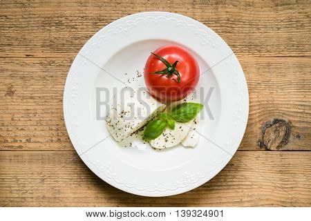 Mozzarella cheese with tomato fresh basil olive oil and herbs as ingredients for caprese salad. Top view.