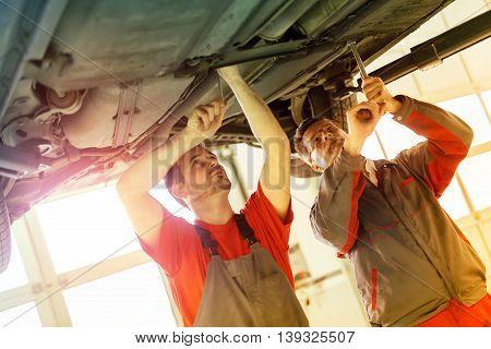 Car mechanics fixing car in garage - teamwork