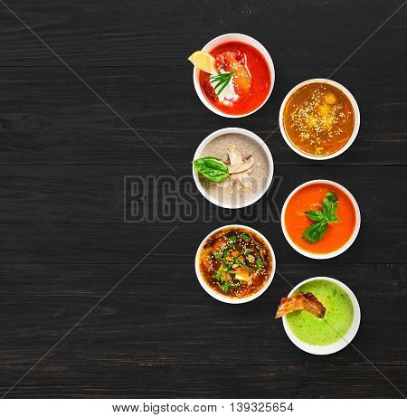 Variety of restaurant hot dishes, healthy food. Japanese miso, asian fish soup, russian borscht, english pea soup with bacon, mushroom soup, spanish gazpacho at black wood, top view with copy space
