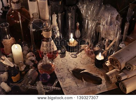 Mystic still life with old parchments papers, vintage bottles, candles, skull and magic objects. Ancient pharmacy, medieval alchemist or witch laboratory