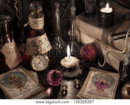 Close up of the tarot cards, warlock book, vintage bottles, books and candles. Halloween concept, black magic ritual or spell with occult and esoteric symbols, divination rite