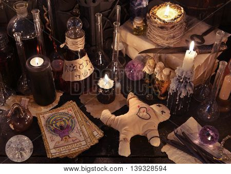 Mystic still life with voodoo doll, the tarot cards, book, evil candles and witchcraft objects. Halloween concept, black magic ritual or spell with occult and esoteric symbols, divination rite
