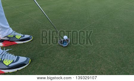 close up of putter hitting golf ball to hole at course