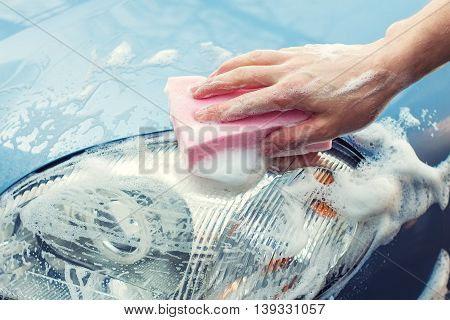 Washing the car by hand with soapy sponge. Cleaning the car. Car care concept. Hand of man washing the car using the sponge with foam