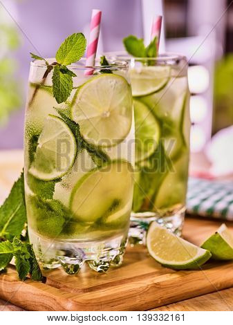 Alcohol cocktail. On wooden boards couple of glasses with alcohol drink and ice cubes. A drink number hundred hundred ninety one cocktail mohito with mint leaf. Country life. Light indoor background.