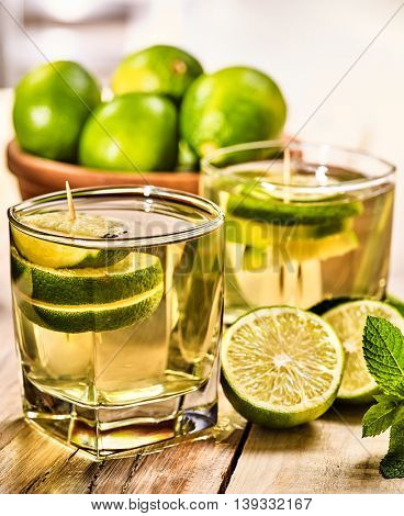 Country drink. On wooden boards is glass with green transparent drink and lime glue bowl. Drink number one hundred eighty five mojito with mint leaf . Country life. Wooden boards background.
