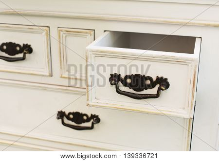 Old wooden antique chest of drawers with metal handles closeup, open drawer shelf. Shabby chic vintage style interior, furniture detail from rustic white wood.