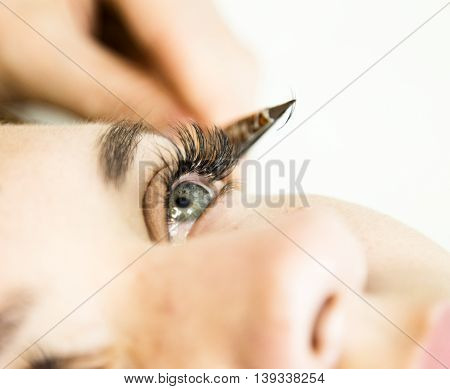 Beautiful young woman with eyelash extension. Woman eye with long eyelashes. Beautician eyelash extension for young woman in a beauty salon.