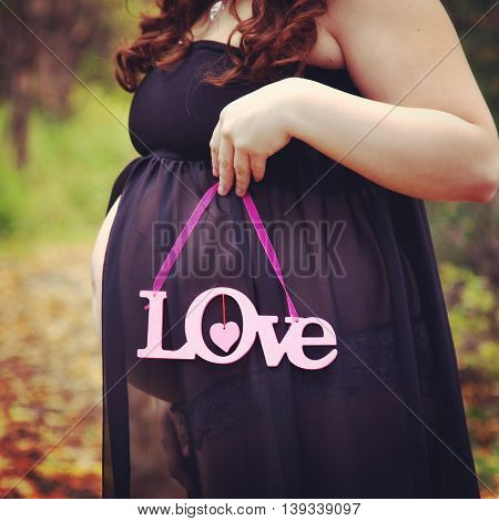 beautiful instagram of pregnant woman holding quote forest path in fall