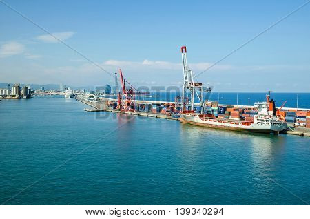 Barcelona Spain - June 2 2016: View of commercial port and cruise terminal with its colorful rail cranes and containers with W Barcelona also known as the Hotel Vela (Sail Hotel) in a background.