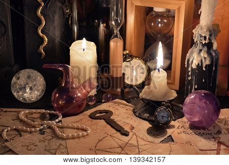 Close up of magic objects, witch book, crystal balls and candles on witch table. Halloween concept, scary ritual or spell with occult and esoteric symbols
