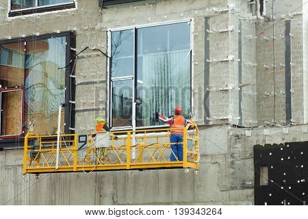 Surveying Large Building Site. Workers Building New House install Windows Wall Insulation Balcony. Industrial Building Construction.