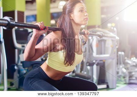 Fit woman doing squat with barbell in the gym