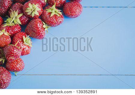 Fresh strawberries on blue wooden background copyspase