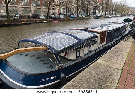 AMSTERDAM NETHERLANDS - NOVEMBER 15 2015: Bark with solar panels on the roof in an amsterdam canal