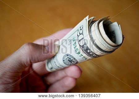 Roll of paper banknotes (American Dollars, USD) hold by a male hand as a symbol of ongoing money transfer (payment, bribery or gift)