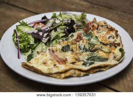 Omelette with mashrooms, bacon and vegetables served with salad