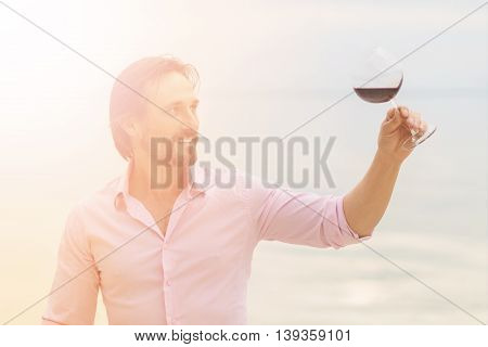 Confident sommelier. Toned image of thoughtful young sommelier holding glass of red wine and looking at it while staying near by sea.