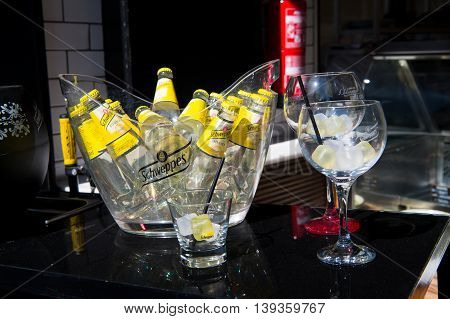 Key west, Fl, USA - March 30 2016: Schweppes Tonic Water bottles yellow color in glass with cold ice cubes on table near bocals of lemon beverage with drinking straw