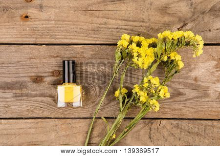 Bottle Of Yellow Nail Polish And Flowers On Brown Wooden Table