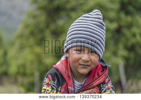 AZUAY, ECUADOR, OCTOBER - 2015 - Portrait of indigenous ecuadorian kid with serious expression in Azuay province Ecuador.