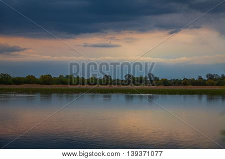 Evening sunset over quiet pond before the storm