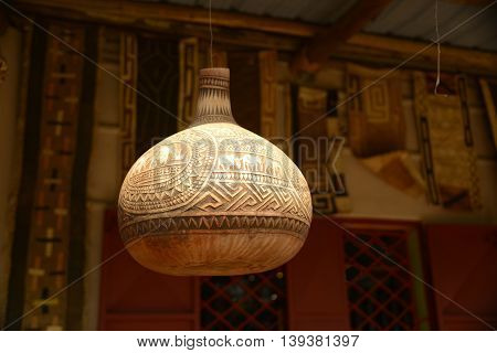 Carved decorative African gourd hanging on porch