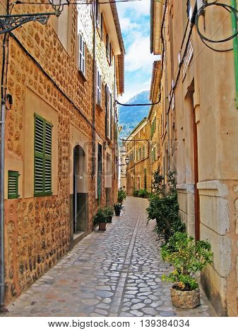 Cobblestone alley in Valldemossa Majorca - between narrow houses - view towards mountains of the Serra de Tramuntana poster