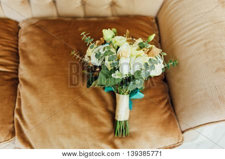 Bridal bouquet of roses on a brown brown chair