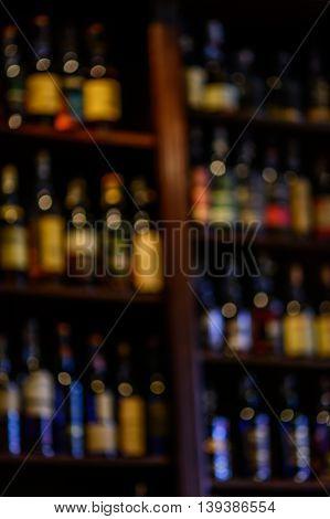 Blurred Of Wine Bottles. Vertical Blurred Image Of Bottles Of Wine On The Shelves In Market..