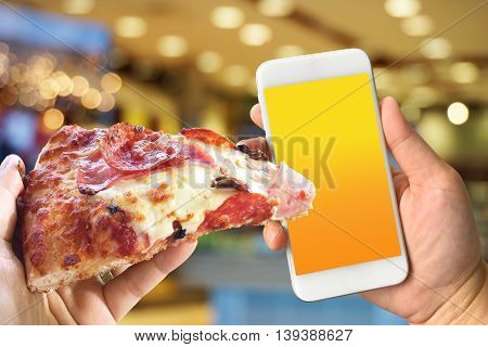 Woman hand holding smartphone against blur colorful bokeh background pizza online concept with copy space
