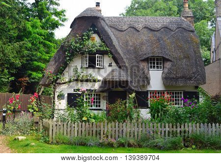 Houghton, Cambridgeshire, England - July 20, 2016: Thatched cottage with white walls and colourful garden.