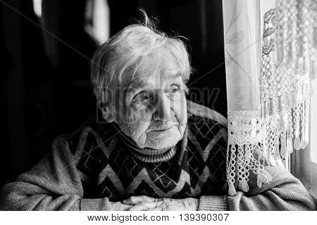Elderly woman portrait looking out the window. Black-and-white photo of high contrast.