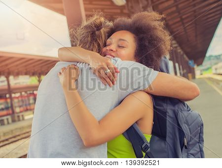 Man meeting his girlfriend from her trip at the train station. Close up.