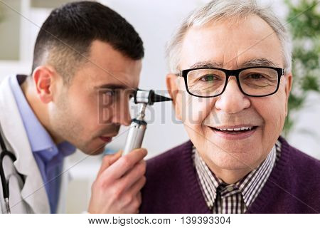 Senior patient visit otologist ear examining, close up